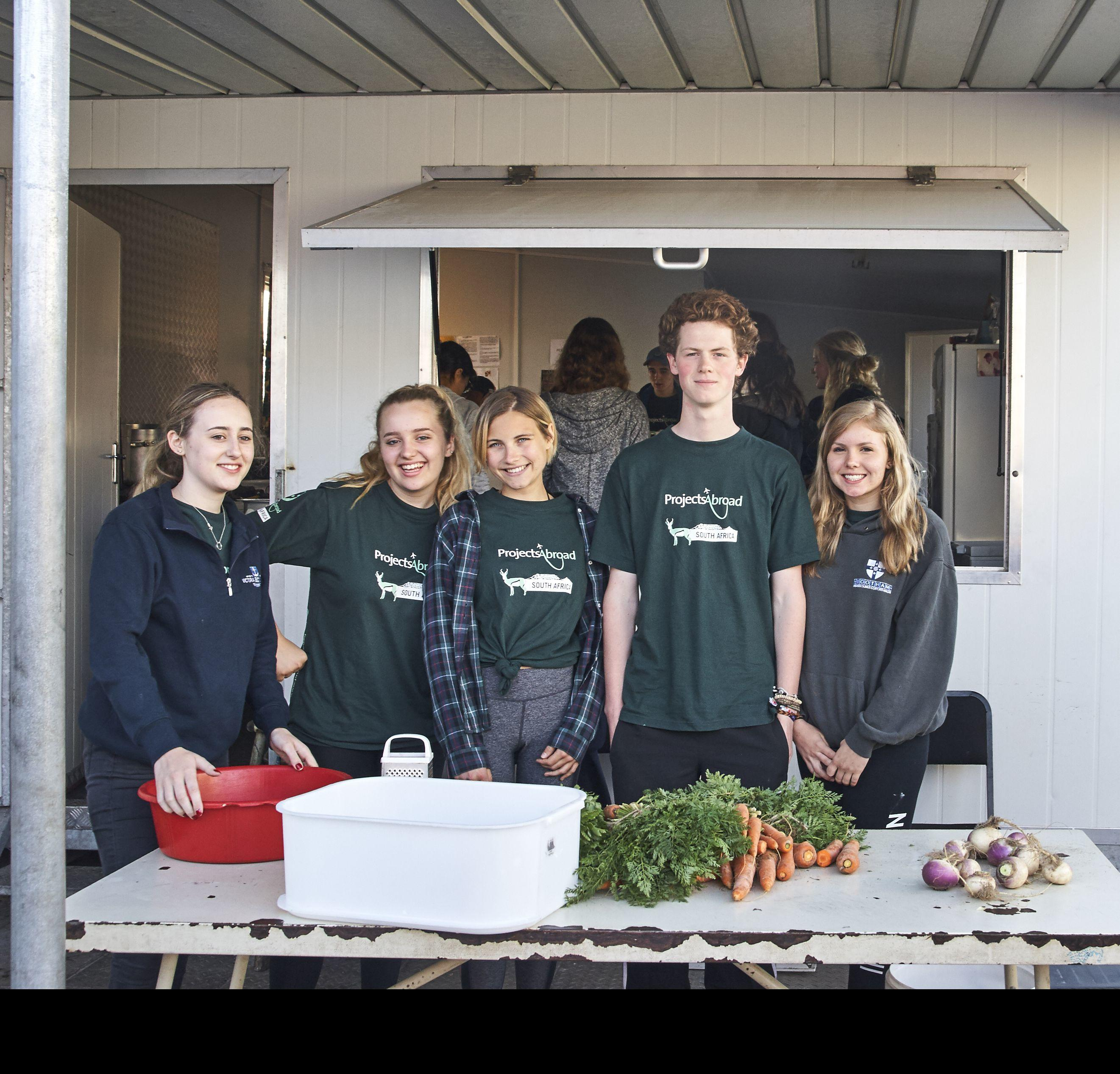 High school students prepare meals during volunteer work in South Africa for teenagers